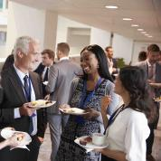 Networking event with people talking huddled in group