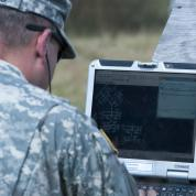 Officer reviewing laptop screen on field